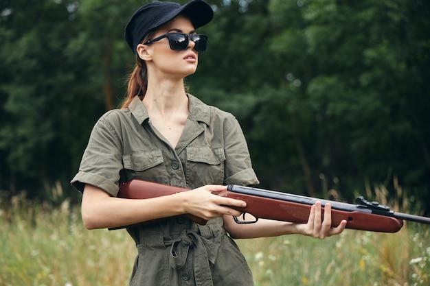 Женщина с ружьем на открытом воздухе в лесу и деревьях зеленой травы