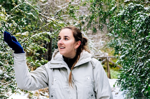 눈 덮인 풍경에 나무를 고민하는 행복한 얼굴을 가진 여자
