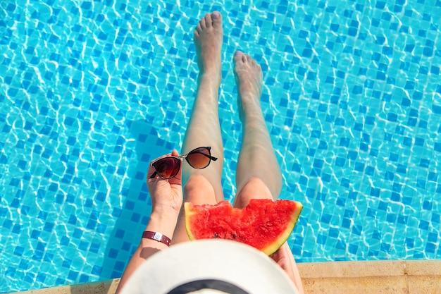 スイミングプールでスイカを食べる帽子とサングラスを持つ女性