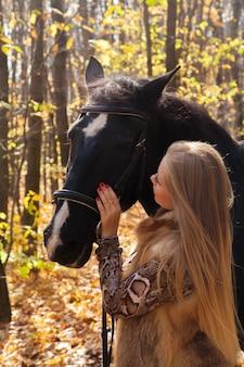 가을 숲에서 산책 말과 함께 여자