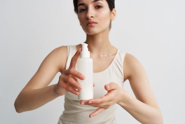 白いtシャツのスキンケアスパトリートメントで彼女の手にローションの瓶を持つ女性