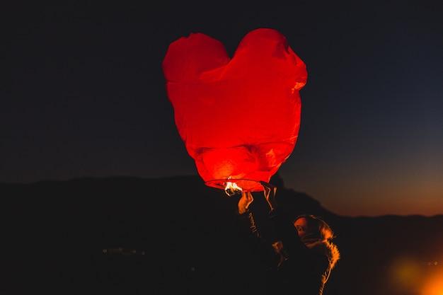 夜に熱い空気の凧を持つ女性