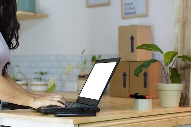 ノートパソコンと一杯のコーヒーを持つ女性
