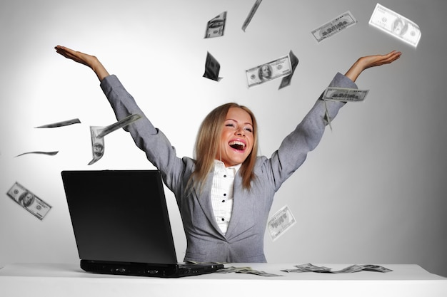 Женщина с ноутбуком и долларовыми купюрами в воздухе
