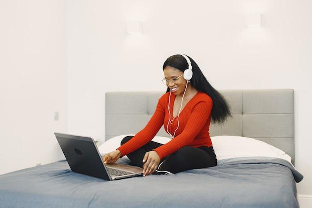 ベッドの上にラップトップを持つ女性