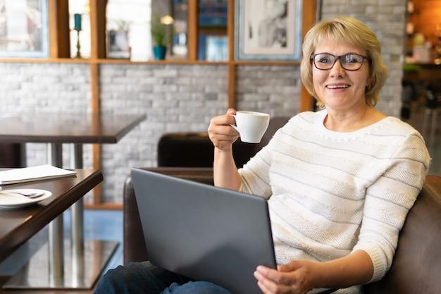 노트북을 가지고 있는 여성은 사무실의 카페에서 일하는 프리랜서입니다.