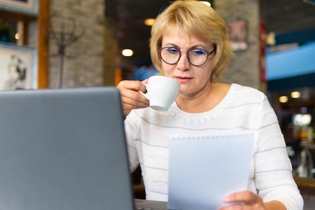 노트북을 가진 여성은 사무실의 카페에서 일하고 프리랜서입니다.