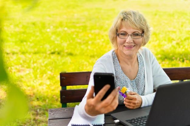 노트북을 가진 여성은 자연의 정원에서 일하며 프리랜서입니다.