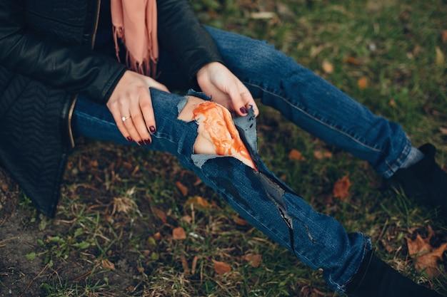 Женщина с травмой ноги. раненая девушка сидит у дерева. рана кровоточит.