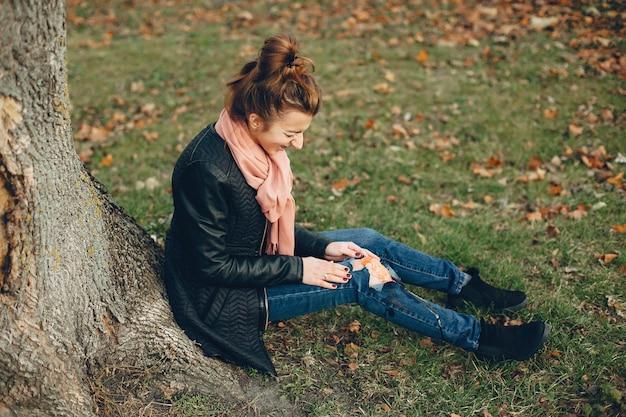 足の怪我をした女性。木のそばに座っている負傷した少女。傷は出血しています。