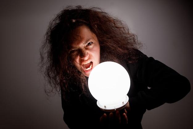 明るいボールを持つ女性。悪魔のような外観