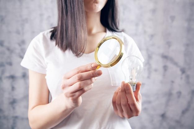 돋보기를 가진 여자는 전구를 살펴 봅니다. 개념 연구 아이디어