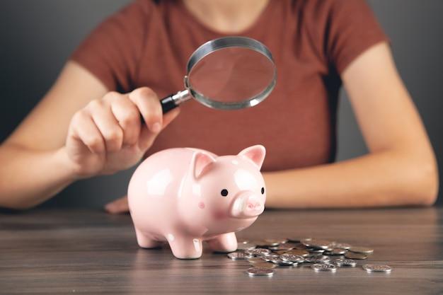 돋보기를 든 여자가 돼지 저금통과 동전을 쳐다본다
