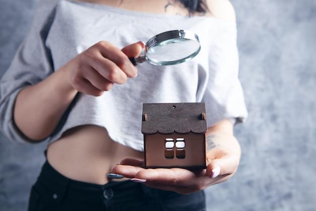 돋보기를 든 여자가 집을 살펴봅니다. 집 검색 개념