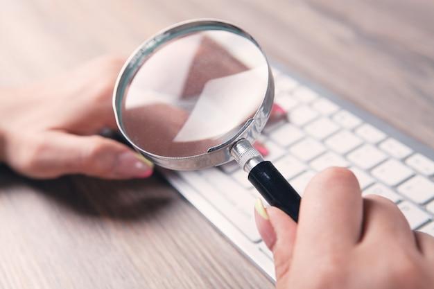 돋보기를 가진 여자는 키보드를 살펴 봅니다. 온라인 검색