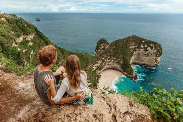 Женщина с мужчиной на пляже келингкинг на нуса пенида, бали, индонезия