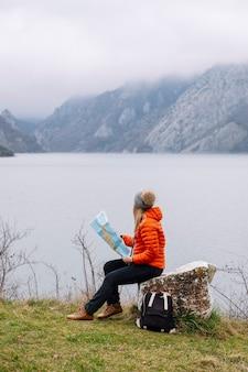 地図を持つ女性、湖のある自然の中で座っている