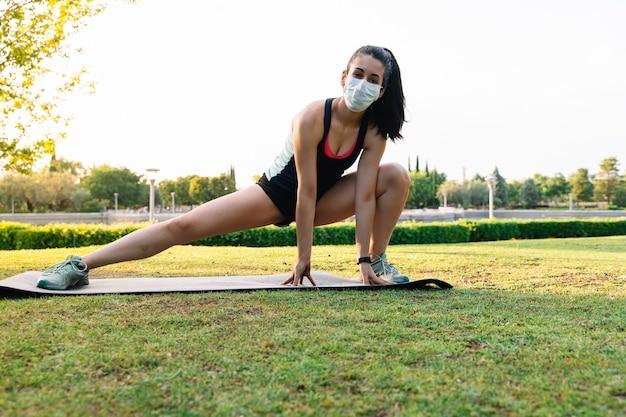 Женщина при маска делая представление йоги пока протягивающ ногу в тюфяке в парке. новая концепция нормальности