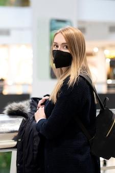 Covid19のマスクを持った女性。友人を待っている、ウイルスからの黒い医療マスクのブロンドの女性。