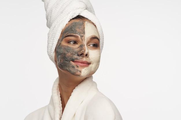 그녀의 얼굴에 마스크를 가진 여자 피부 관리 미용 스파 절차 그녀의 머리에 피부과 흰 가운 수건
