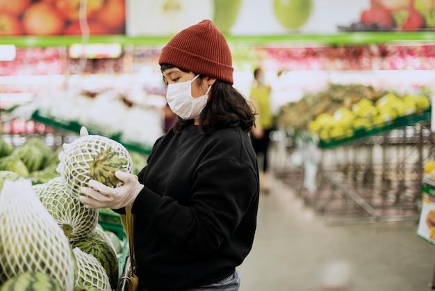 コロナウイルスのパンデミック中に生鮮食品を購入する医療マスクを持つ女性