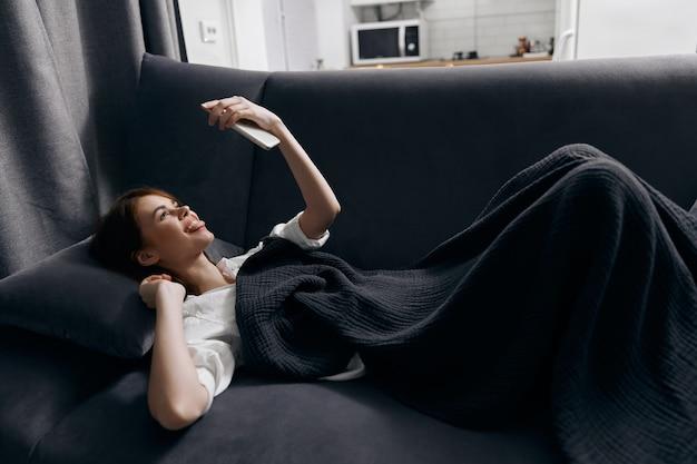 그녀의 눈 앞에서 휴대 전화를 가진 여자는 소파 평면도에 놓여 있습니다. 고품질 사진