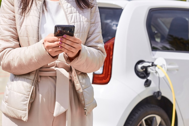 전기 자동차 충전 근처 휴대 전화를 가진 여자. 야외 공공 충전소에서 충전하는 차량. 자동차 공유 개념