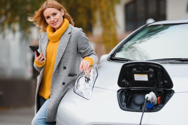 電気自動車の充電の近くで携帯電話を持っている女性。屋外の公共充電ステーションでの車両充電。カーシェアリングのコンセプト