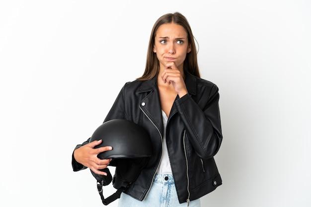 オートバイのヘルメットをかぶった女性が疑問を抱き、考えている