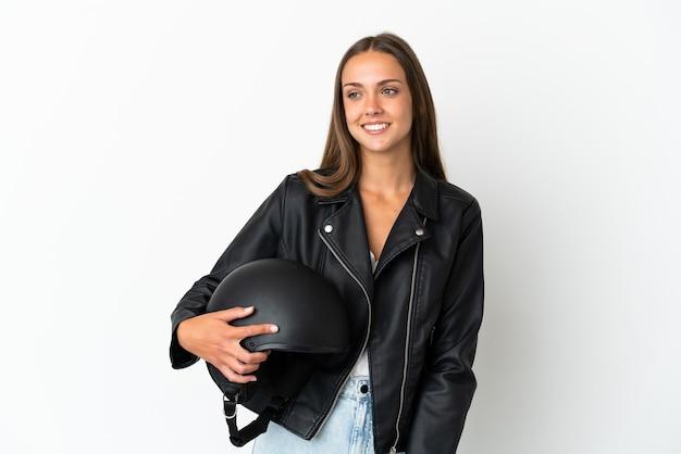 横を向いて笑顔で孤立したオートバイのヘルメットをかぶった女性
