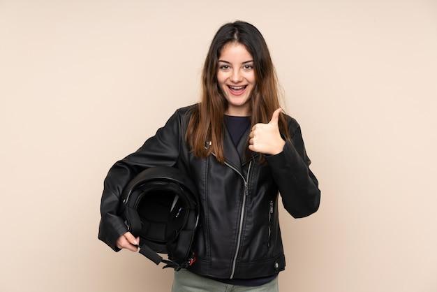 親指のジェスチャーを与えるベージュの壁にオートバイのヘルメットを持つ女性