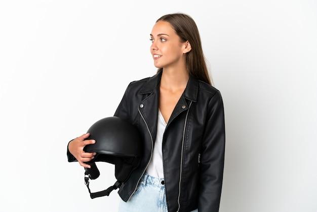 側面を見て孤立した白い背景の上のオートバイのヘルメットを持つ女性