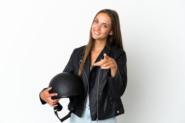 Женщина с мотоциклетным шлемом на изолированном белом фоне, указывая спереди с счастливым выражением лица