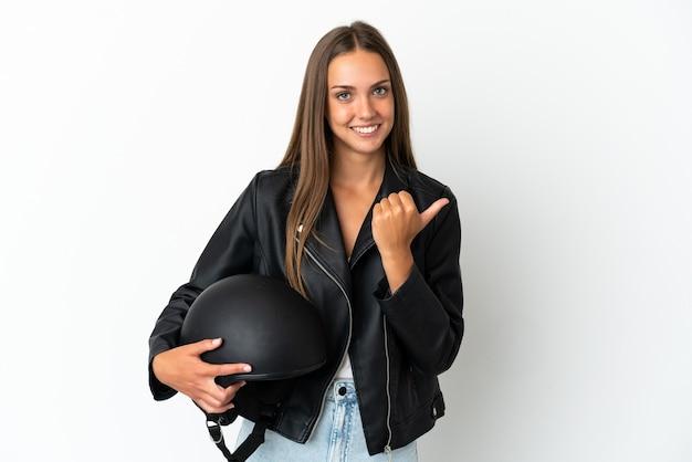 製品を提示する側を指している孤立した白い背景の上にオートバイのヘルメットを持つ女性