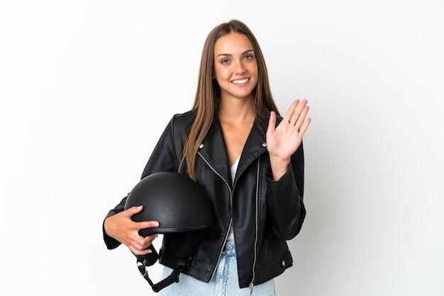 孤立した白い背景の上にオートバイのヘルメットを持つ女性が幸せな表情で手で敬礼