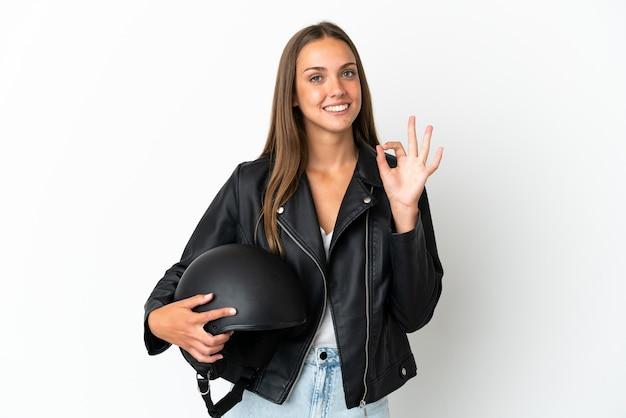 Женщина в мотоциклетном шлеме на изолированном белом фоне, показывая пальцами знак ок