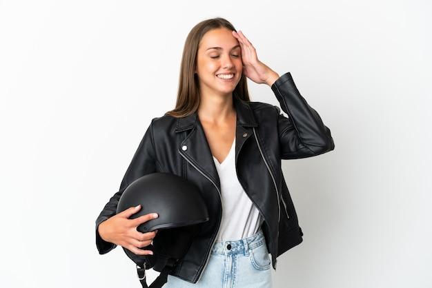 たくさん笑って孤立した白い背景の上のオートバイのヘルメットを持つ女性