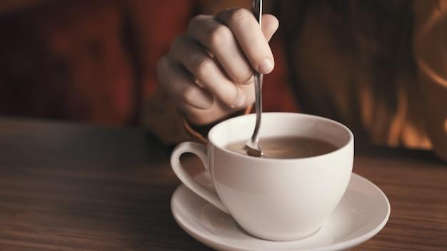 テーブルでお茶のマグを持つ女性