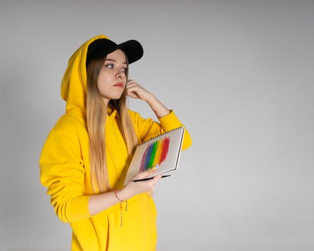 Женщина с блокнотом, на котором изображена радуга лгбт, девушка поправляет волосы