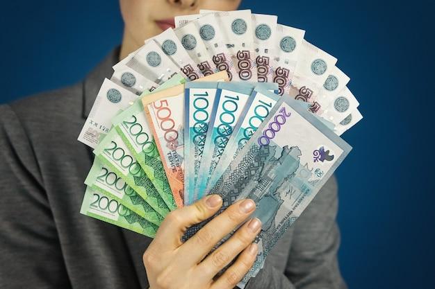 Женщина с пачкой казахстанских тенге и российских рублей в руке крупным планом иммиграционная концепция