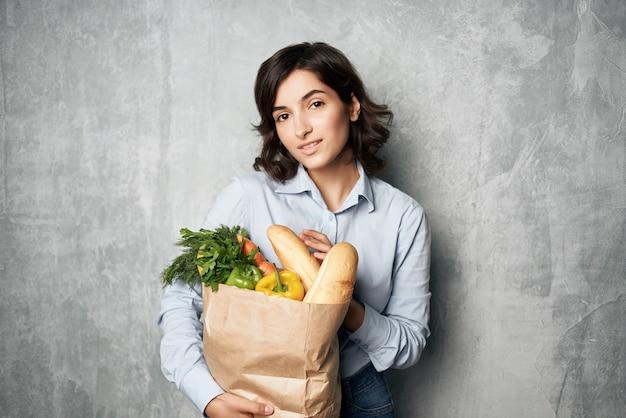 食料品配達ショッピングサービスのパッケージを持つ女性