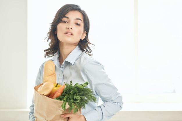 キッチンで食料品のパッケージを持つ女性主婦野菜健康食品