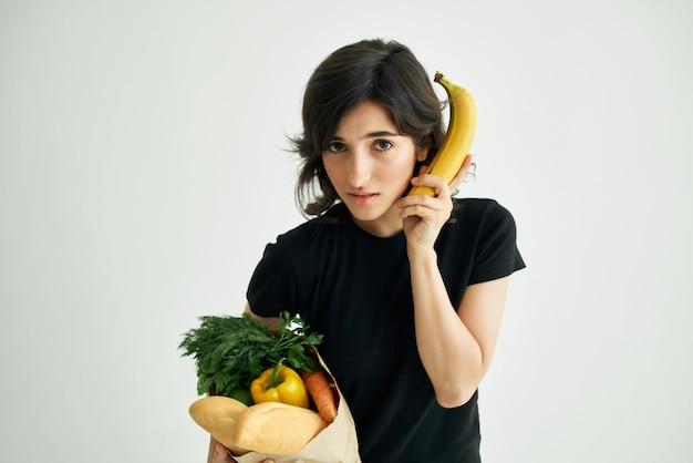 健康食品店で買い物をする食料品のパッケージを持つ女性