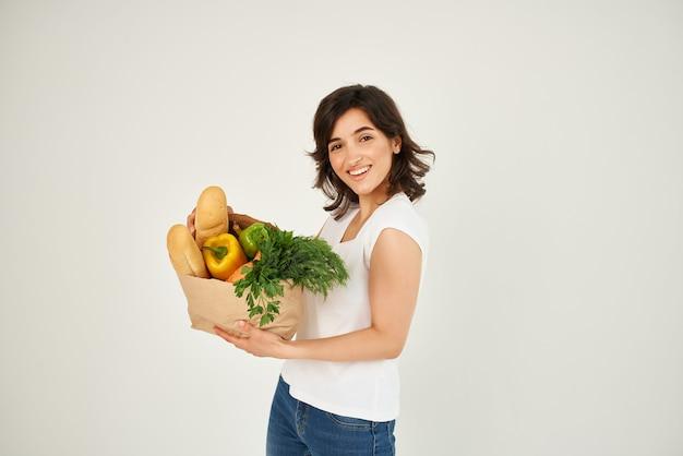 Женщина с пакетом продуктов, делая покупки в супермаркете светлом фоне