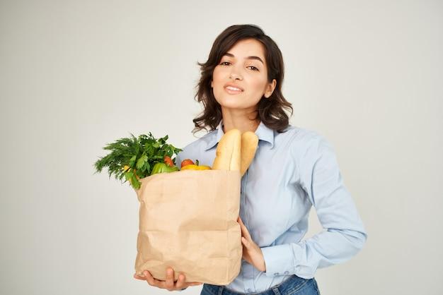 野菜の食料品スーパーマーケットのクローズアップのパッケージを持つ女性