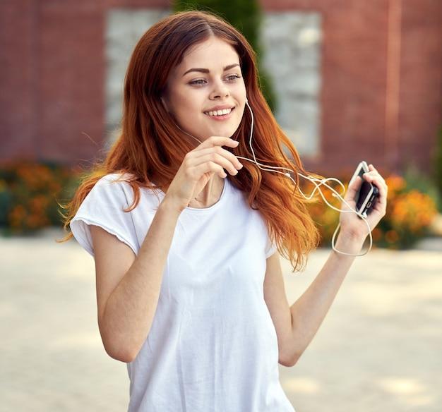電話とイヤホンを持つ女性