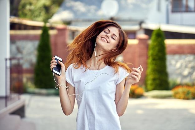 電話とヘッドフォンを持つ女性
