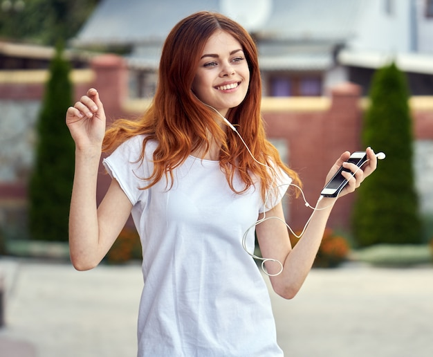 Женщина с телефоном в наушниках бежит