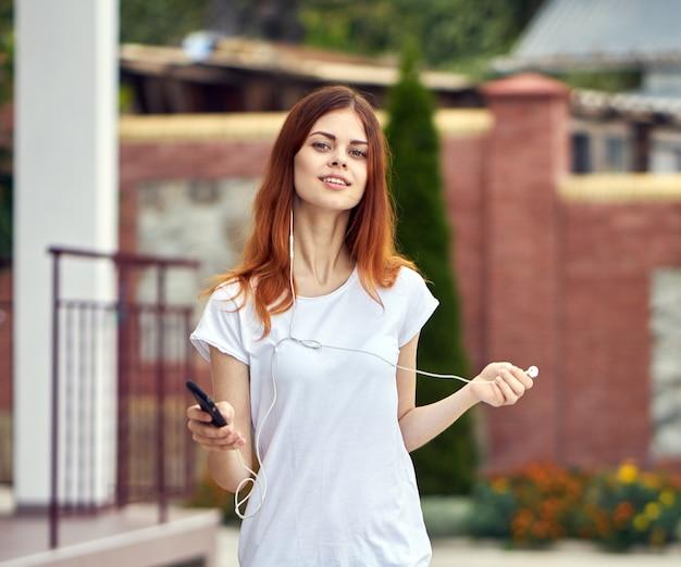 ヘッドフォンで携帯電話を持つ女性