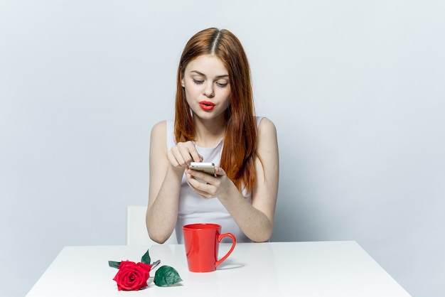 장미 꽃과 함께 테이블을 촬영 그녀의 손에 전화를 가진 여자